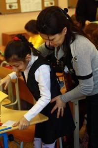 Учитель помогает ученице с ограниченными возможностями здоровья